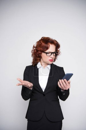 confused businesswoman looking at smartphone