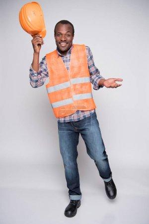Photo pour Plan complet d'un travailleur de la construction heureux dans un gilet posant et levant son casque . - image libre de droit
