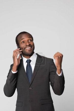 Cheering businessman talking on phone