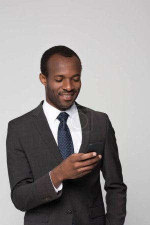 Smiling businessman looking at smartphone