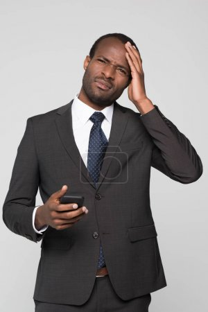businessman touching his head and squinting
