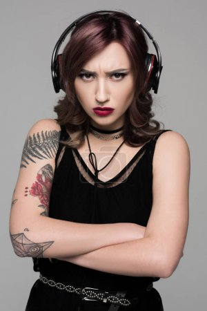 Grumpy young woman in big headphones