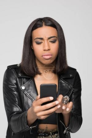 Young woman typing on smartphone