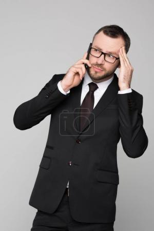 Young businessman on phone touching his temple