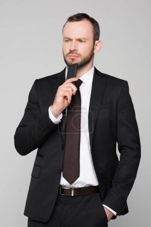 Photo for Half-length shot of young businessman in a suit holding his smartphone to his chin with a pensive look on his face. - Royalty Free Image