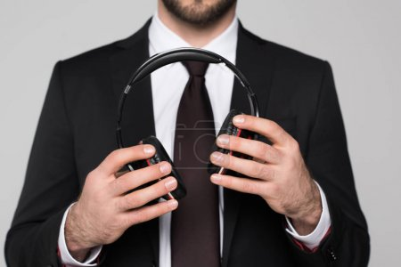 young businessman holding headphones in hands