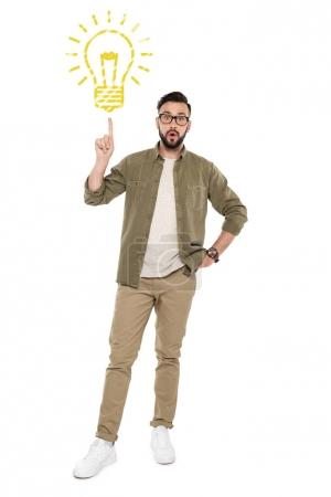 Photo for Young man looking at camera while pointing up at cartoon light bulb with finger isolated on white - Royalty Free Image