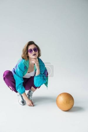 Photo pour Portrait d'une femme à la mode dans les lunettes de soleil et vêtements vintage une assise près de ballon isolé sur fond gris - image libre de droit