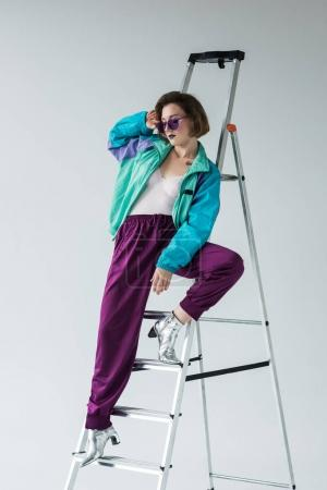 stylish woman leaning on ladder