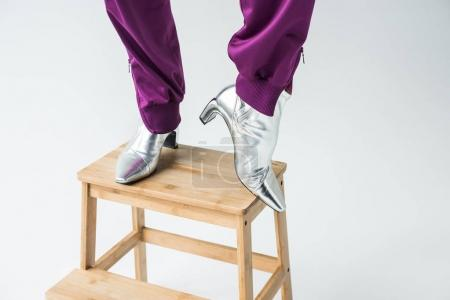 Photo for Close-up shot of woman in silver colored boots standing on stepledder - Royalty Free Image