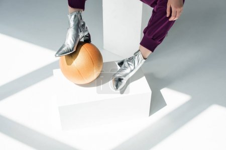 Photo for Cropped shot of woman in silver colored boots with basketball ball - Royalty Free Image