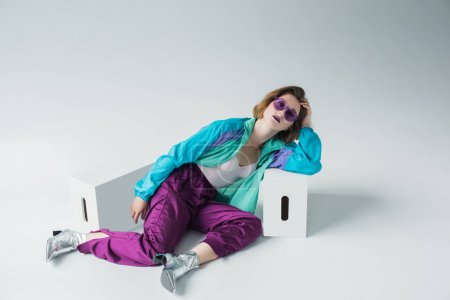 Photo for Fashion portrait of stylish young girl in sport suit and high heels laying on floor - Royalty Free Image
