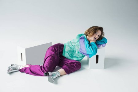 Photo for Fashion portrait of young girl in sport suit and high heels laying on floor - Royalty Free Image