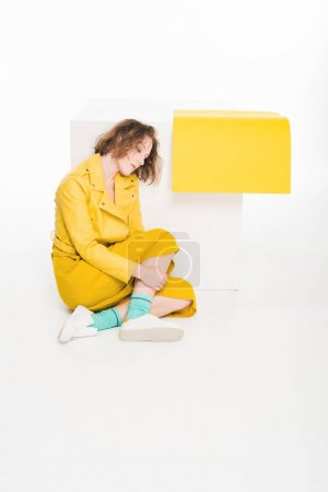 Photo for Fashion portrait of sad young girl dressed in all yellow with yellow paper - Royalty Free Image