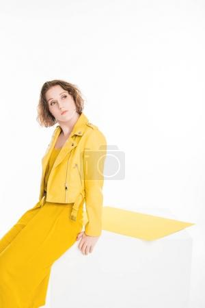 Photo for Fashion portrait of thoughtful young girl dressed in all yellow with yellow paper isolated on white - Royalty Free Image