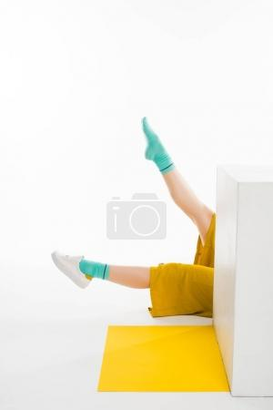Photo for Female legs in yellow pants and turqouise socks behind white cube isolated on white - Royalty Free Image