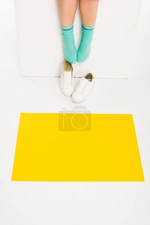 Photo for Feet of girl in turqouise socks with white shoes and yellow square on floor - Royalty Free Image