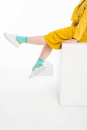 Photo for Cropped shot of girl dressed in yellow with turqouise socks sitting on white cube isolated on white - Royalty Free Image
