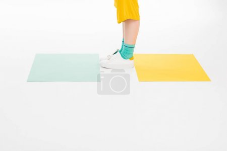 Photo for Cropped shot of girl dressed in yellow with turqouise socks isolated on white with colored papers - Royalty Free Image