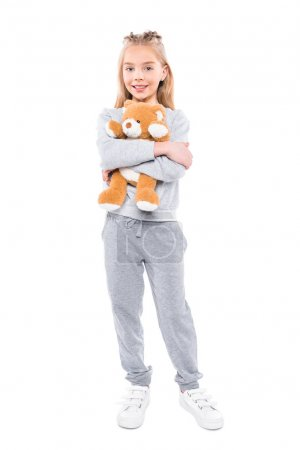 Photo for Adorable little girl hugging teddy bear and smiling at camera isolated on white - Royalty Free Image