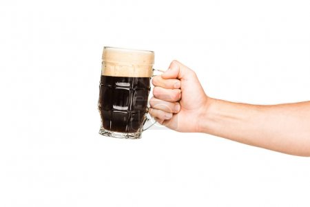 Cropped view of person holding glass of dark beer,...