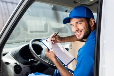 Photo for Smiling delivery man filling in documents on clipboard at car - Royalty Free Image