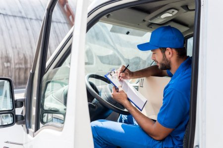 Photo for Young delivery man filling in documents on clipboard at car - Royalty Free Image