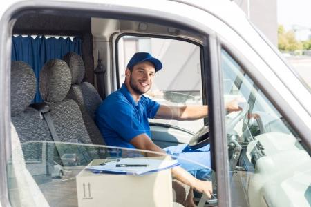 Photo for Happy handsome delivery man sitting in car - Royalty Free Image