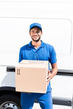 Photo for Smiling delivery man with box next to car - Royalty Free Image