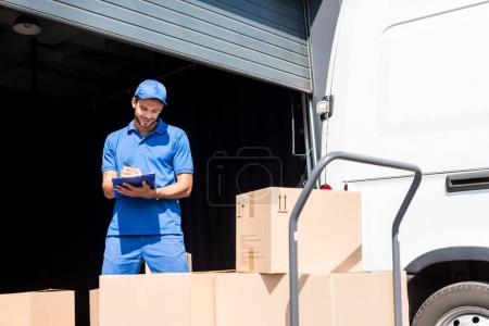Photo for Delivery man writing in clipboard next to warehouse - Royalty Free Image