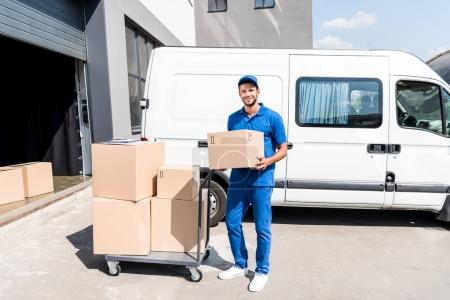 Photo for Delivery man with box and cart next to van - Royalty Free Image