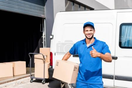 Photo for Smiling delivery man with box showing thumb up - Royalty Free Image