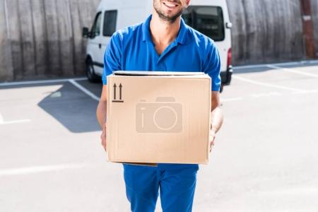 Photo for Close-up shot of smiling delivery man carrying cardboard box - Royalty Free Image