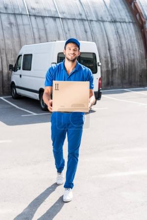 Photo for Smiling delivery man carrying cardboard box - Royalty Free Image