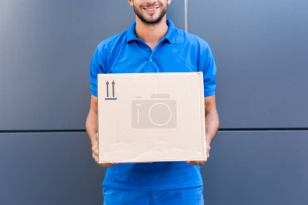 Photo for Delivery man holding cardboard box and smiling - Royalty Free Image