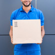Delivery man holding cardboard box and smiling...