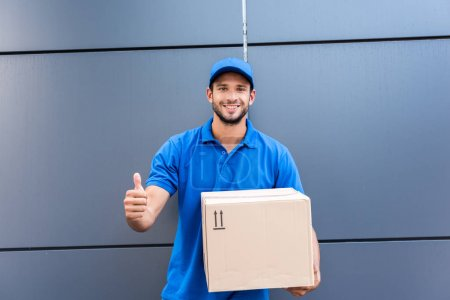 Photo for Delivery man with box showing thumb up - Royalty Free Image