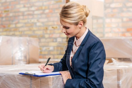 Photo for Young businesswoman signing document in warehouse - Royalty Free Image