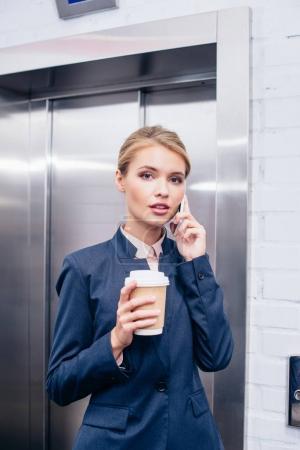 Photo pour Femme d'affaires de parler par téléphone et tenant une tasse jetable de café - image libre de droit