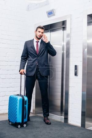 businessman with suitcase next to elevator