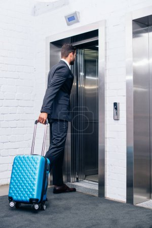 businessman with suitcase entering elevator