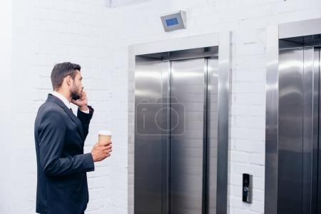 businessman talking by phone with coffee
