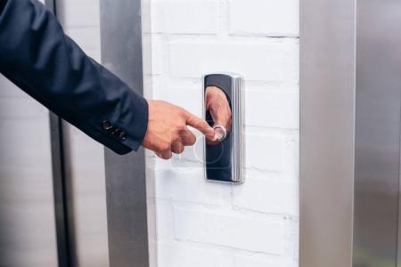 homme en costume en appuyant sur le bouton d'ascenseur
