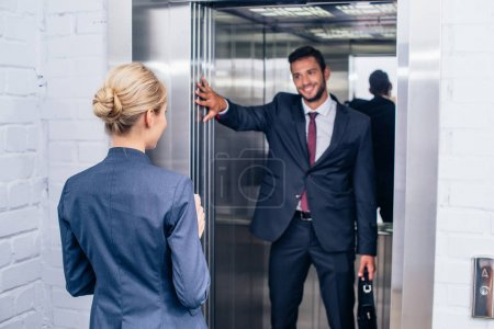 Smiling handsome businessman holding elevator door...