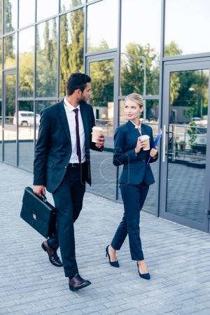 Photo pour Les gens d'affaires marchant à l'extérieur avec des tasses jetables de café - image libre de droit