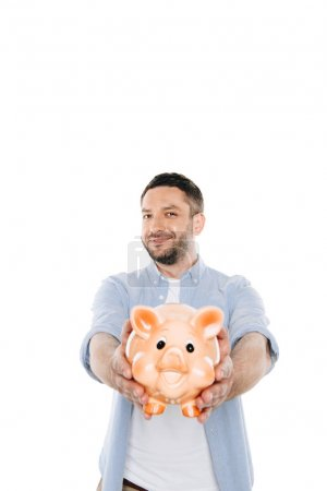 Photo for Cheerful bearded man holding piggy bank and smiling at camera isolated on white - Royalty Free Image