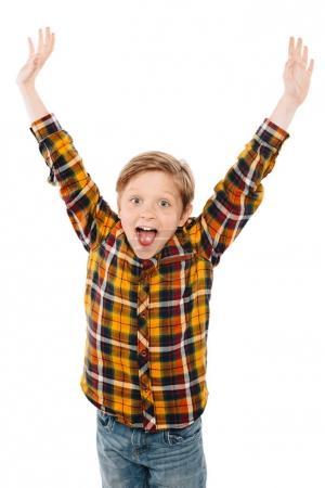 Foto de Niño emocionado levantando las manos y sonriendo a cámara aislada en blanco - Imagen libre de derechos