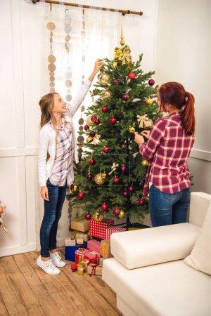 Photo pour Heureuse mère et fille décoration sapin de Noël ensemble à la maison - image libre de droit