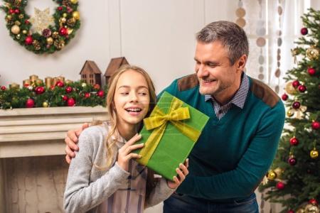 Foto de Padre sonriente mirando hija feliz Linda celebración de Navidad en casa - Imagen libre de derechos