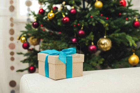 Photo for Close-up view of gift box with blue ribbon and christmas tree indoors - Royalty Free Image